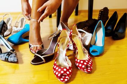 Frau mit vielen Schuhen zur Auswahl