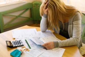 Eine Frau mit offenen Rechnungen hat viele Schulden. Arbeitslosigkeit und Privatkonkurs