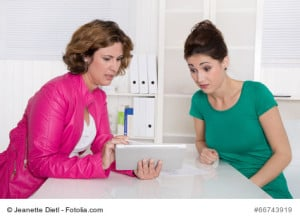 Job interview or business meeting under two woman sitting at desk: adviser and customer.