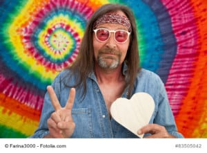 Hippie middle-aged peaceful man wearing red headband, sunglasses and blue denim shirt while making the victory sign and holding a white handmade heart shape, portrait on spiral colorful background