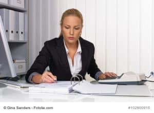 Eine Buchhalterin bei der Arbeit im Büro mit Taschenrechner